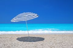 Sun umbrella on a pebble beach with turquoise sea Stock Photography