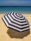 Sun umbrella on a sandy beach. Against emerald sea and blue sky Stock Photography