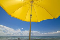 Sun umbrella on a sandy seashore on a hot July day. People are swimming in the sea royalty free stock photography