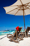 Sun umbrella with Santa Claus Hat on chairs Royalty Free Stock Photography