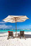 Sun umbrella with Santa Claus Hat on chairs Stock Images