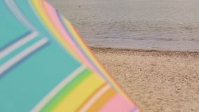 Sun umbrella waving in nice weather at beach background. Copy space at right stock video footage