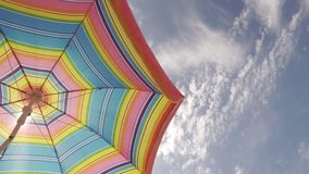 Sun umbrella waving in nice sunny weather at sky background. Copy space at right stock footage