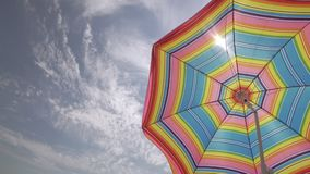 Sun umbrella waving in nice sunny weather at sky background. Copyspace at left stock footage