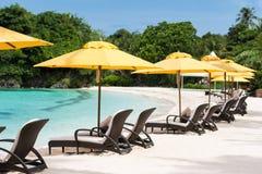 Sun umbrellas and beach chairs on beach Stock Photo