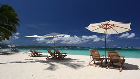 Sun umbrellas and beach chairs on coastline with white sand. Boracay. Philippines stock video footage