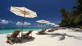 Sun umbrellas and beach chairs on coastline with white sand. Boracay