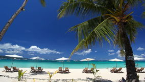 Sun umbrellas and beach chairs on coastline with white sand. Boracay, Philippines stock footage