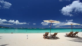 Sun umbrellas and beach chairs on coastline with white sand. Boracay, Philippines stock video footage