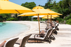Sun umbrellas and beach chairs on tropical beach Stock Photography
