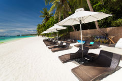 Sun umbrellas and beach chairs on tropical coast Stock Photo