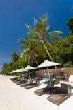 Sun umbrellas and beach chairs on tropical coast Stock Photos