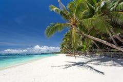 Sun umbrellas and beach chairs on tropical coast. Boracay Royalty Free Stock Photos