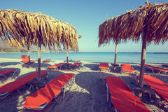 Sun umbrellas and chairs on beach Stock Images