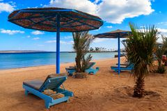 Sun umbrellas and chaise lounges on tropical beach. Concept of rest, relaxation, holidays, resort. Sun umbrellas and chaise lounges on the tropical beach stock photography