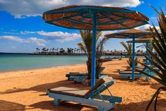 Sun umbrellas and chaise lounges on tropical beach. Concept of rest, relaxation, holidays, resort. Sun umbrellas and chaise lounges on the tropical beach royalty free stock photo