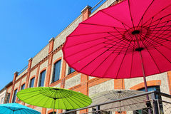 Sun umbrellas in the city. Low-angle shot of sun umbrellas in vivid colors in the city against a blue sky. Summer season Royalty Free Stock Image