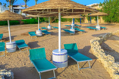 Sun umbrellas and empty deckchairs on the shore sand beach Stock Photo