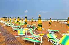 Sun umbrellas and loungers in the deserted Beach in summer Royalty Free Stock Photos