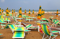 Sun umbrellas on sea beach with sun loungers and deckchairs Royalty Free Stock Photography