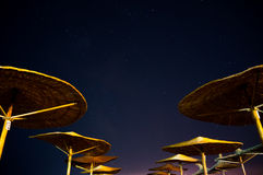 Sun umbrellas during starry night in Vama Veche beach Stock Photos