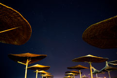 Sun umbrellas during starry night in Vama Veche beach Royalty Free Stock Image