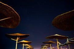 Sun umbrellas during starry night in Vama Veche beach royalty free stock image