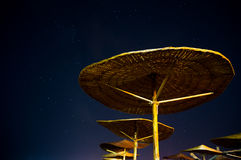 Sun umbrellas during starry night in Vama Veche beach Stock Photo