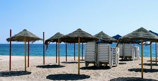 Sun umbrellas and sunbeds in the sand. On the shore of the mediterranean sea stock image