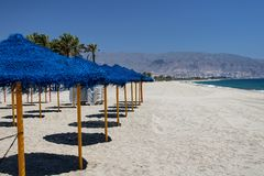 Sun umbrellas and sunbeds in the sand. On the shore of the mediterranean sea royalty free stock image