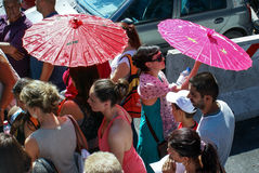 Sun umbrellas. Tourists in sun light of Rome with red umbrellas Royalty Free Stock Images