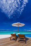 Sun umbrellas and wooden beds on tropical beach with the best vi Stock Photography
