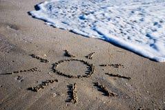 Sun-umreiß auf dem nassen Sand Stockfoto