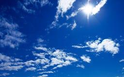 Sun und Wolken auf blauem Himmel Stockbild