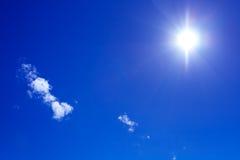 Sun und Wolken auf blauem Himmel Lizenzfreies Stockfoto