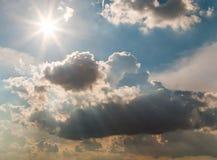 Sun und Wolken auf blauem Himmel Stockbilder