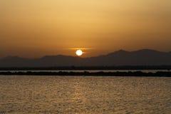 The Sun uppsättningar bak bergen Royaltyfria Bilder
