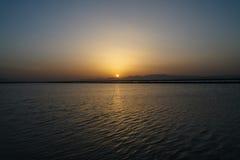 The Sun uppsättningar bak bergen Royaltyfri Bild