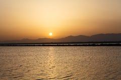 The Sun uppsättningar bak bergen Arkivfoto
