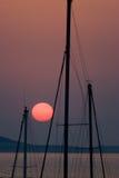 Sun vermelho e mastros Imagem de Stock