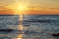Sun w chmurach przy zmierzchem nad morzem Fotografia Royalty Free