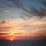 Sun w chmurach przy zmierzchem nad morzem Zdjęcia Stock