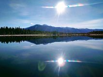 Sun in the water of the taiga lake royalty free stock photo