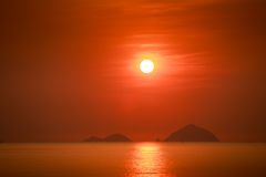Sun white disk among red sky above sea islands at sunrise Royalty Free Stock Photos