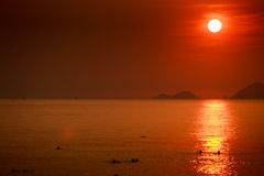 Sun white disk among red sky above sea islands at sunrise Stock Image