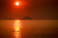 Sun white disk among red sky above sea islands at sunrise Royalty Free Stock Images
