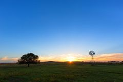 The sun, a windmill and a lone tree Royalty Free Stock Photos