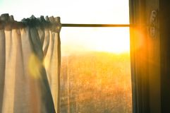 Sun through window with curtains. Warm sunlight through window with curtains in train or house. Sunbeam of sunset or dawn Stock Photos