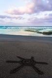Sun-Zeichen gezeichnet auf schwarzen Sand des Strandes Stockbilder