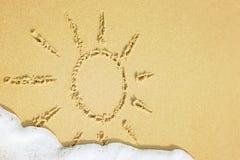 Sun-Zeichnung gezeichnet auf einen Strand auf dem goldenen Sandhintergrund mit Seewelle und Schaum auf Sommerferien am Erholungso lizenzfreies stockbild
